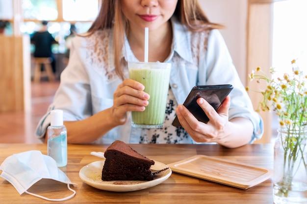 カフェでスマートフォンを使用しながらアイス抹茶ラテを飲む美しい若いアジアの女性。
