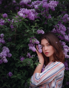 Beautiful young asian woman enjoying the blooming of flowers lilac in spring. nude make up. close up portrait