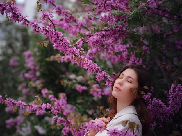 Красивая молодая азиатская женщина наслаждаясь цветением цветков весной. обнаженный макияж. портрет крупным планом