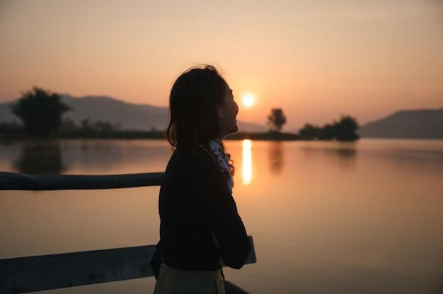 Красивая молодая азиатская женщина наслаждаясь восходом солнца на горном озере утром