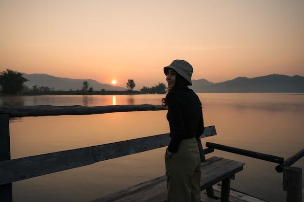 아침에 산 호수에서 일출을 즐기는 아름 다운 젊은 아시아 여자
