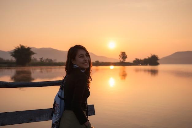산 호수에서 일출을 즐기는 아름 다운 젊은 아시아 여자