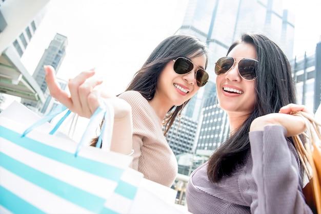Beautiful young asian woman friends enjoying shopping in the city