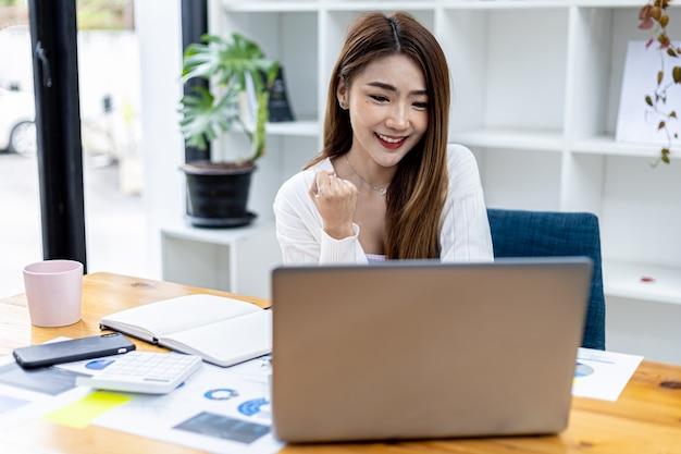 노트북 앞에서 몸짓을 하는 아름다운 젊은 아시아 여성, 똑똑하고 현대적인 여성 임원, 스타트업 비즈니스 여성, 비즈니스 리더 여성으로 일하는 아시아 여성의 개념 이미지.