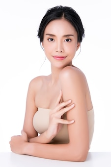 Beautiful young asian woman hand touching on shoulder. clean and fresh skin,, beauty cosmetology concept