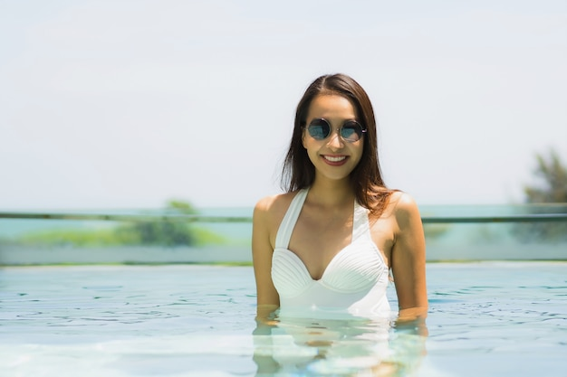 Beautiful young asian woman happy and smile in swimming pool for relax travel and vacation
