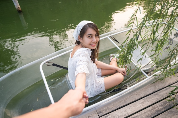 Beautiful young asian woman holding hands with boyfriend to pull up from transparent boat on canal