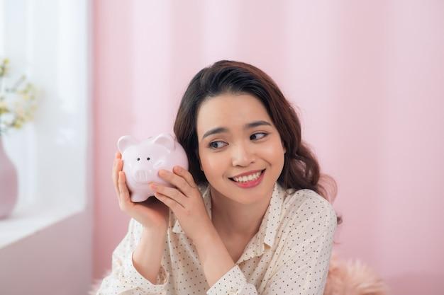 Красивая молодая азиатская женщина, держащая копилку над розовой стеной.