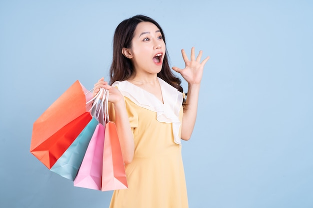 Beautiful young asian woman holding shopping bag on blue background
