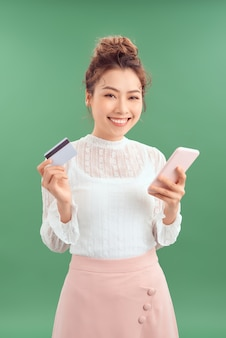 Красивая молодая азиатская женщина, держащая смартфон и кредитную карту на зеленом фоне.