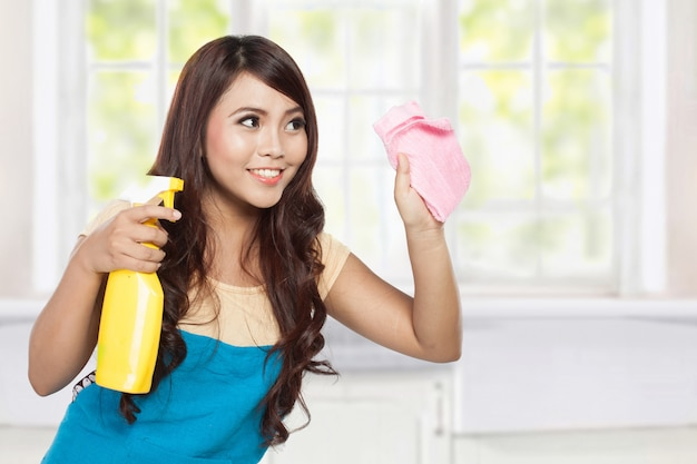Beautiful young asian woman holding sprayer and cleaning