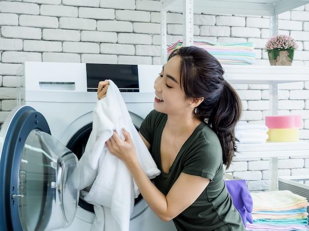 Красивая молодая азиатская женщина-домохозяйка сидит с улыбающимся и пахнущим белым чистым полотенцем после стирки из стиральной машины в прачечной.