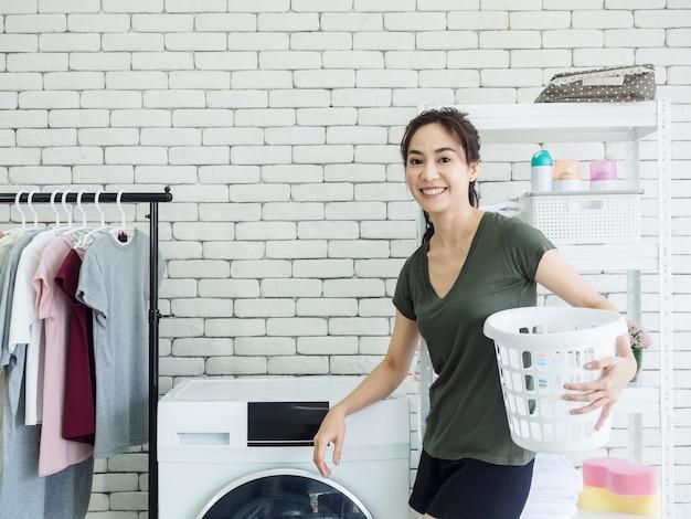 Красивая молодая азиатская домохозяйка женщины стоя и держа пустую корзину белой ткани с усмехаясь около стиральной машины в прачечной.