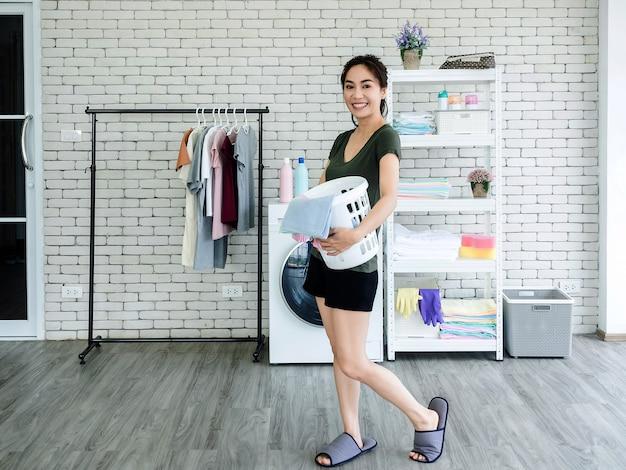 Красивая молодая азиатская домохозяйка женщины стоя и держа белую корзину ткани с усмехаясь около стиральной машины в прачечной.