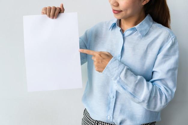 青いシャツを着た美しい若いアジアの女性は、広告のために手に白紙を持っています