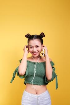 音楽を聴き、黄色の背景で歌うヘッドフォンで美しい若いアジアの女性