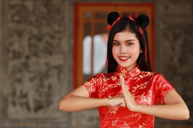 Красивая молодая азиатская женщина в красном китайском платье традиционного чонсам ципао с жестом поздравления и счастливым улыбающимся лицом, она стоит перед древней стеной (концепция китайского нового года)