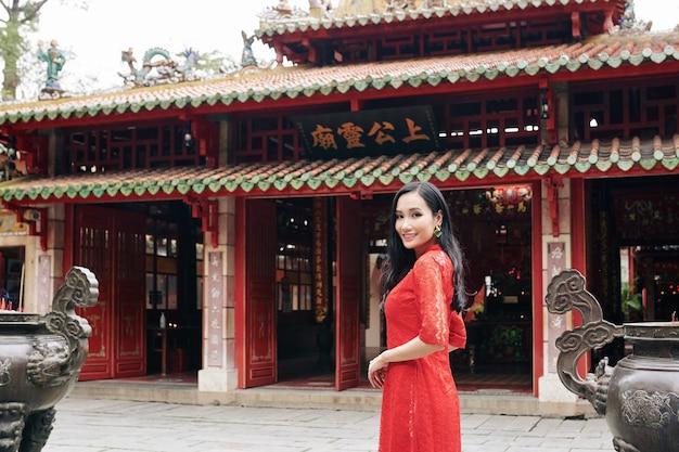 Красивая молодая азиатская женщина в красном кружевном платье стоит в буддийском храме и улыбается в камеру