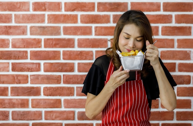 붉은 줄무늬 앞치마를 입은 아름다운 젊은 아시아 여성이 벽돌 벽 근처에 맛있는 감자 튀김 체를 들고 요리 기술을 만족시키고 맛있는 음식을 먹도록 설득하는 것으로 자랑스럽게 미소를 보여줍니다.