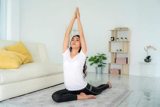 Красивая молодая азиатская женщина в спортивной одежде делает йогу во время отдыха в гостиной дома