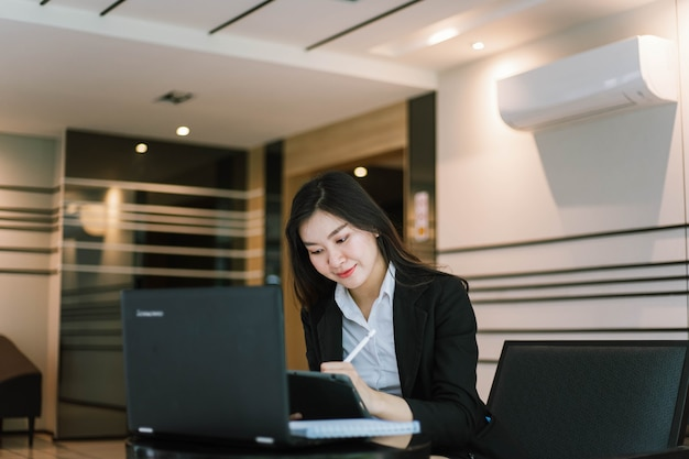 ノートパソコンを使用してメモを書くスーツの美しい若いアジアの女性