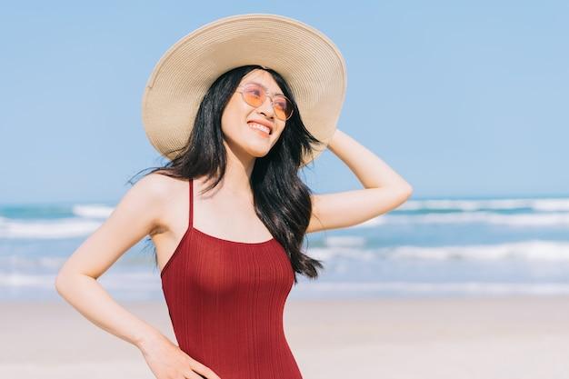 夏休みの間にビーチでリラックスした水着の美しい若いアジアの女性