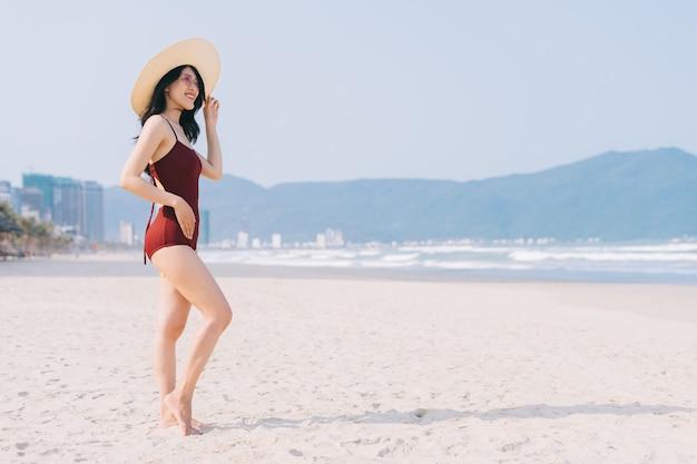 여름 방학 동안 해변에서 편안한 수영복에 아름 다운 젊은 아시아 여자