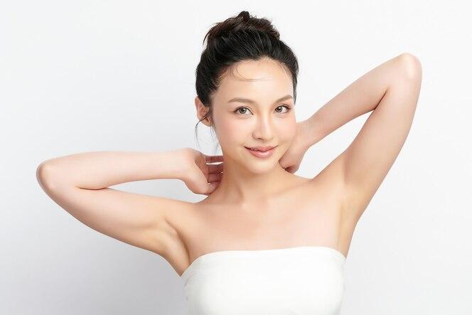 美しい若いアジアの女性が手を上げて、白い背景に清潔で衛生的な脇の下または脇の下を披露します。滑らかな脇の下の清潔さと保護の概念