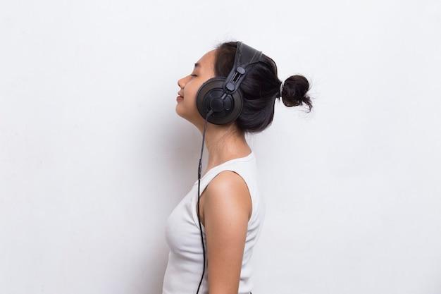 흰색 배경에 고립 된 음악을 듣고 아름 다운 젊은 아시아 여자