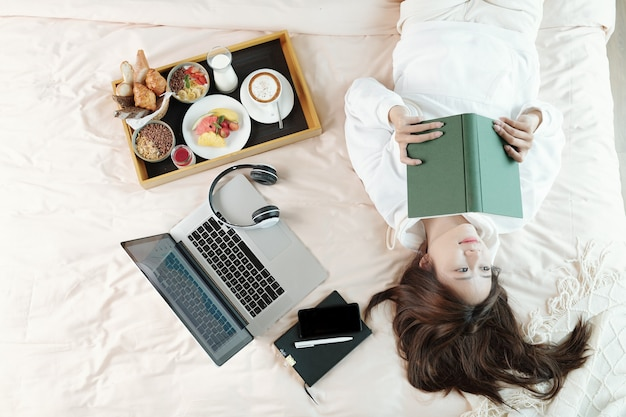 Beautiful young asian woman lying on bed next to laptop and breakfast tray and thinking after reading thought-provoking article in book
