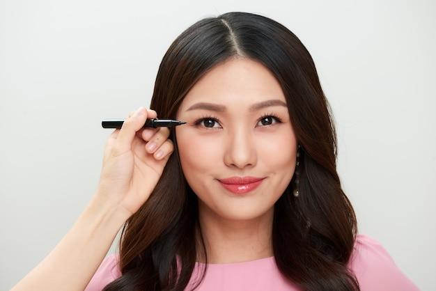 黒のアイライナーで美しい若いアジアの女性のメイクアップ。