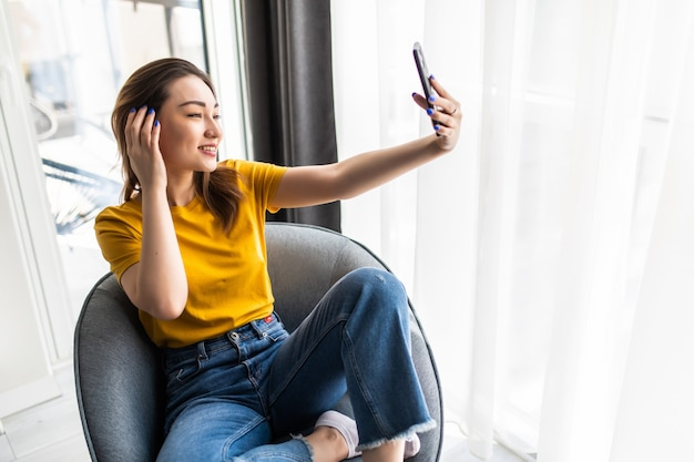 Beautiful young asian woman making selfie by her smart phone and smiling while sitting in big comfortable chair at home