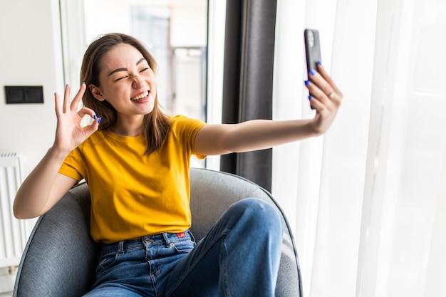 Bella giovane donna asiatica che fa selfie con il suo smartphone e sorride mentre è seduta su una sedia grande e comoda a casa