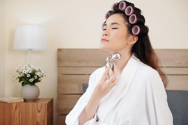 주름을 없애기 위해 금속 롤러로 목을 마사지하는 아름다운 젊은 아시아 여성