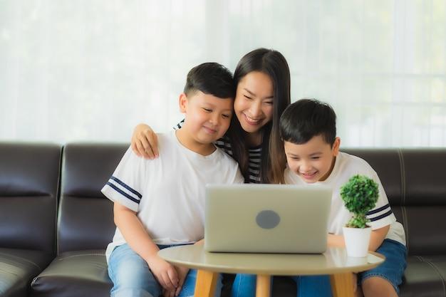 노트북을 사용하는 그녀의 아들과 함께 아름 다운 젊은 아시아 여자 엄마