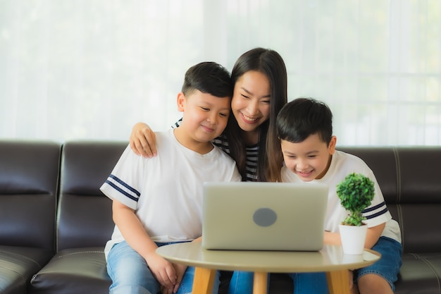 Beautiful young asian woman mom with her sons using a laptop