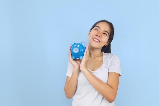 貯金箱を保持するいると青いパステル背景に美しい若いアジア女性。金融貯蓄とお金の富の概念。コピースペース。
