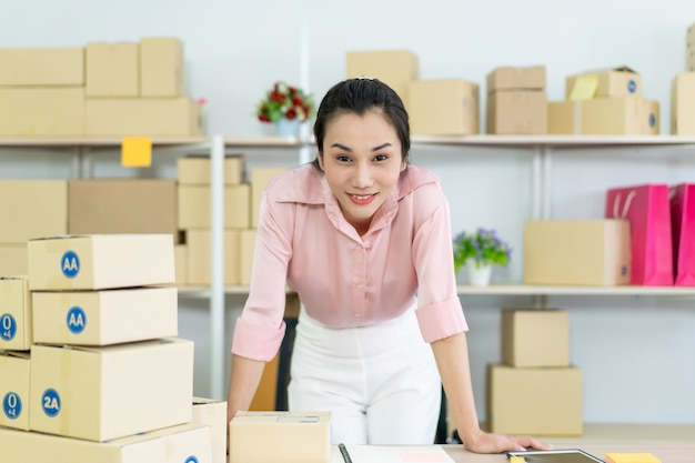 Beautiful young asian woman online seller packing and checking for incoming orders in the warehouse