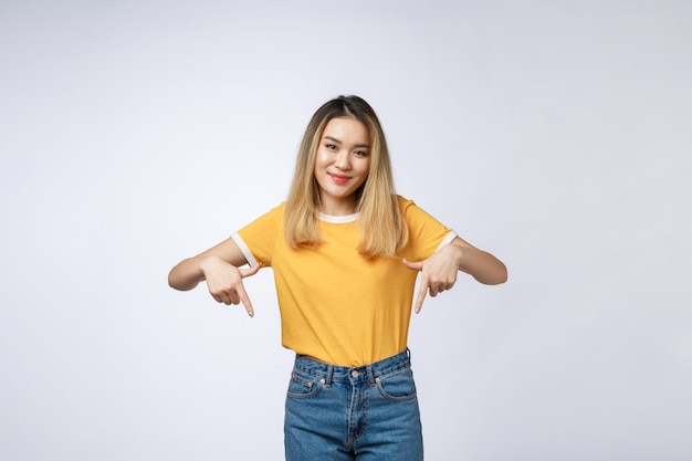 Beautiful young asian woman point down to blank space on grey background.
