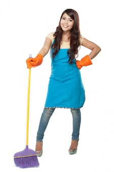 Beautiful young asian woman posing hold onto a broom, while smil
