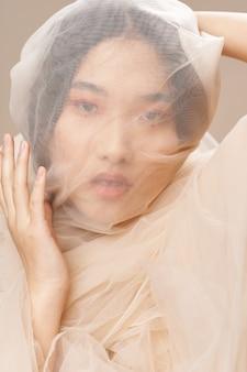 세련 된 옷을 입고 포즈를 취하는 아름 다운 젊은 아시아 여성