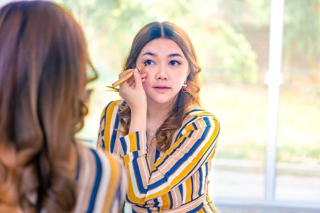 Красивая молодая азиатская женщина надевает макияж перед ее большим окном спальни