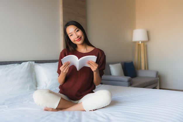 Beautiful young asian woman reading book on bed