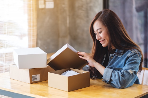 A beautiful young asian woman receiving and opening a postal parcel box at home for delivery and online shopping concept