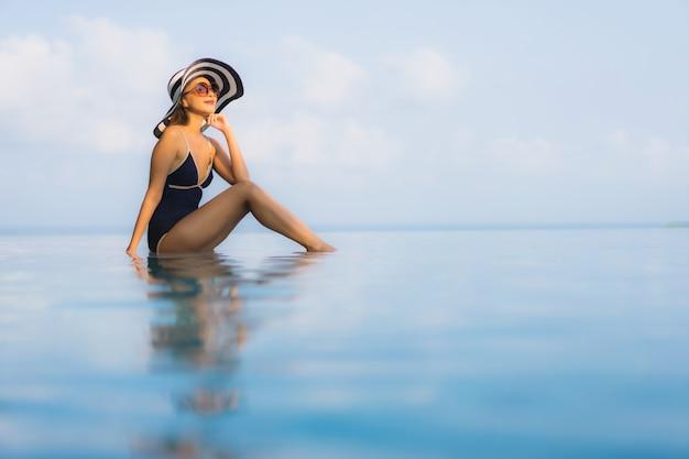 美しい若いアジア女性は、ホテルリゾートのスイミングプールの周りリラックスします。