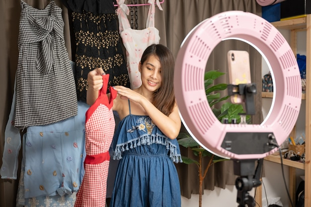 Beautiful young asian woman selling clothes online live streaming by smartphone in the house