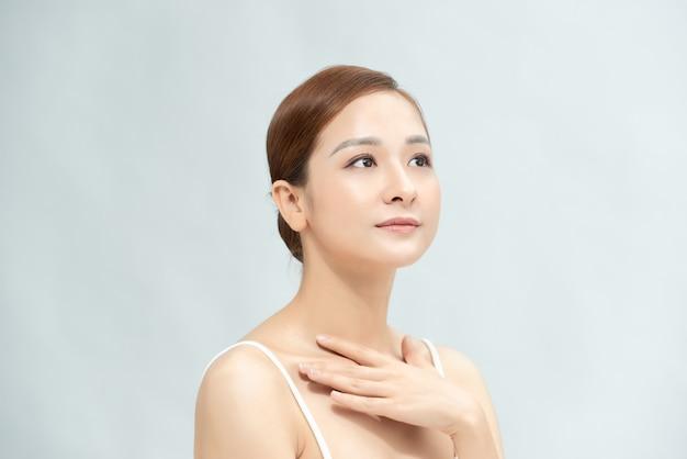 クリアで新鮮な体肌、ナチュラルメイクを示す美しい若いアジアの女性