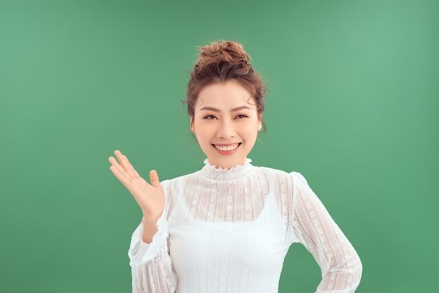 孤立した緑の背景を笑顔しながら彼女の手を示す美しい若いアジアの女性。