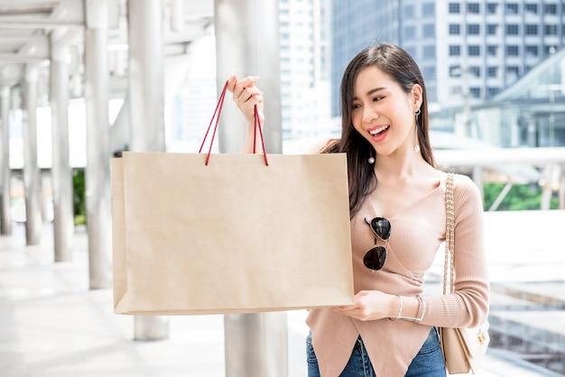Beautiful young asian woman showing her shopping bag