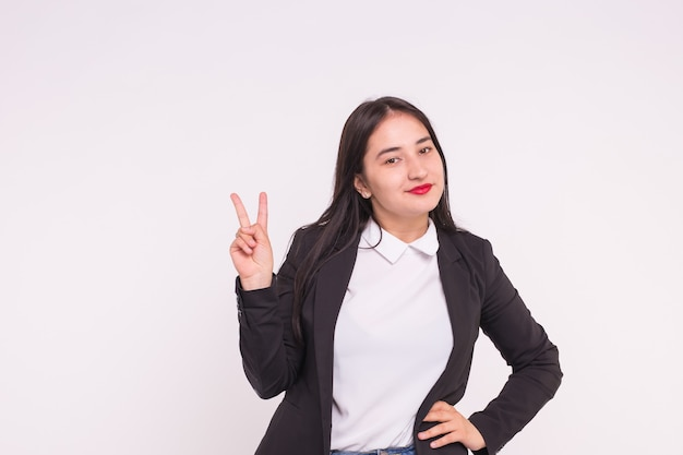 Beautiful young asian woman showing victory sign on white with copy space.